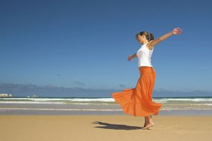 dancing woman on beach in eco living magazine article on NLP.